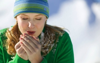 Woman Blowing into Cold Hands --- Image by © Tim Pannell/Corbis